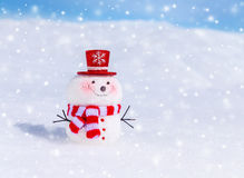 Cute snowman outdoors. In snowy weather, traditional winter symbol, little smiling snowman wearing red hat and scarf, Christmas greeting card Royalty Free Stock Photo