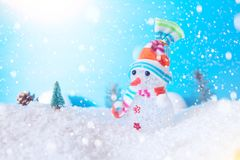 Cute snowman in the snow over blue wooden background Royalty Free Stock Photography
