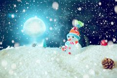 Cute snowman in the snow over blue wooden background. The elements of this image furnished by NASA Royalty Free Stock Photo