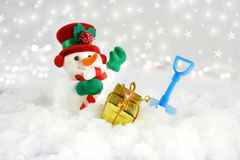Cute snowman in snow with shovel and gift Stock Photo