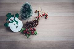 Cute snowman, tiny pine tree, pinecones, glitter holly berries a stock photography