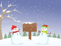 Cute snowman with wooden sign Royalty Free Stock Photography