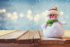 Cute snowman on wooden table. Snow overlay.  royalty free stock photos