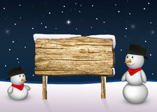 Cute Snowmen with a blank wooden sign Stock Photos