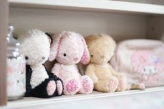 Cute soft plushes. Lovely dolls are sitting on the little girl`s. Headboard and other cute accessories. Selective focus on kawaii pink bunny doll soft plush royalty free stock images