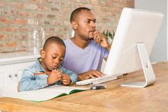 Cute son doing his homework with father. In living room royalty free stock photography
