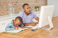 Cute son doing his homework with father. In living room royalty free stock photos