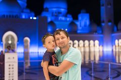 Cute son and father dreaming at the grand mosque of Sheikh Zayed Mosque in Abu Dhabi wearing abaya, paranja in night time. Travell. Ing. Concept for advertising Royalty Free Stock Photo