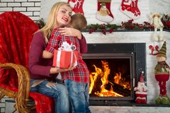 Merry Christmas and Happy Holidays!Cute son gives his beloved mother a gift.New year`s interior in the living room. Cute son gives his beloved mother a gift.New Stock Images
