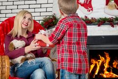 Merry Christmas and Happy Holidays!Cute son gives his beloved mother a gift.New year`s interior in the living room. Cute son gives his beloved mother a gift.New Royalty Free Stock Photo