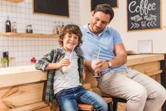 Cute son and his father drinking milkshakes. In cafe Stock Images