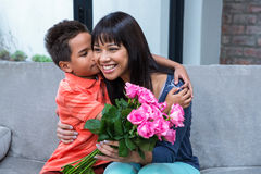 Cute son hugging his mother after giving her flowers. In living room royalty free stock image