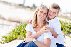 Cute Son Hugs His Mom at The Beach. Cute Son Hugs His Attractive Mom Portrait at The Beach Stock Photos