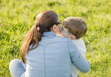 Cute son kissing to his mother sitting in a field. Back view of cute son kissing to his mother sitting in a sunny field Royalty Free Stock Image