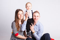 Cute son with parents in studio. Background Stock Photo