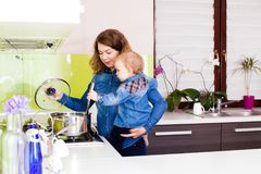 Cute family is preparing food together. Cute son trying to help her mother to make a meal Stock Photography