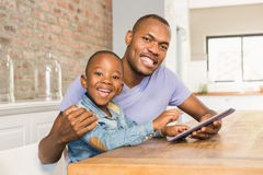 Cute son using tablet at desk with father Stock Photo
