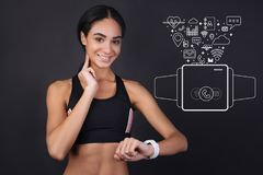 Cute sportswoman measuring her pulse and smiling. Measuring pulse. Young beautiful sportswoman touching her neck and looking at the smart watch while measuring stock image