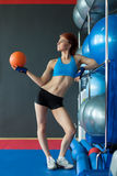 Cute sportswoman posing with balls in gym Stock Photo