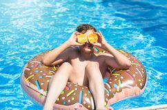 Cute sporty boy swims in the pool with donut ring and has fun, smiles, holds oranges. vacation with kids, holidays, active weekend stock photography