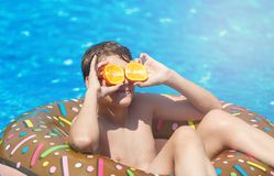 Cute sporty boy swims in the pool with donut ring and has fun, smiles, holds oranges. vacation with kids, holidays, active weekend royalty free stock photo