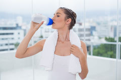 Cute sporty brunette hydrating. After exercising in bright fitness studio Stock Photo