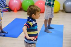 Cute sporty kid exercising on yoga mats in gym, children sport school concept. Cute sporty caucasian kid exercising on yoga mats in gym, children sport school stock photos