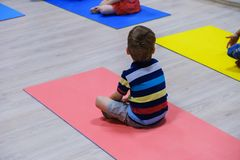 Cute sporty kid exercising on yoga mats in gym, children sport school concept. Cute sporty caucasian kid exercising on yoga mats in gym, children sport school royalty free stock photos