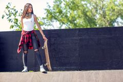 Sporty teen girl with skateboard. Outdoors, urban lifestyle royalty free stock photos