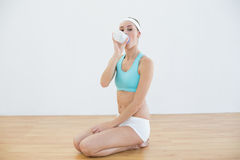 Cute sporty woman sitting on floor drinking from sports bottle Stock Image
