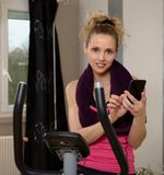 Cute sporty woman using her smartphone. Cute sporty blonde woman using her smartphone Royalty Free Stock Photos