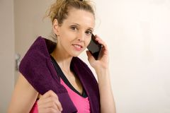 Cute sporty woman using her smartphone. Cute sporty blonde woman using her smartphone Royalty Free Stock Image