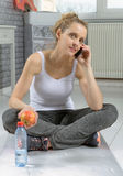 Cute sporty woman using her smartphone. Cute sporty blonde woman using her smartphone at home Stock Images