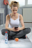 Cute sporty woman using her smartphone. Cute sporty blonde woman using her smartphone at home Stock Image