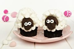Cute spring sheep cupcakes on pink plate with Easter eggs. Against white wood stock photo