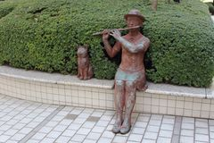 Cute statue of girl playing flute and dog Tokyo Japan Royalty Free Stock Photo