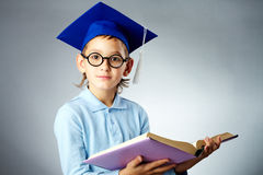 Cute student. Portrait of cute lad in eyeglasses and student hat holding open book Royalty Free Stock Images