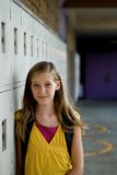 Cute Student. Cute preteen, teen or tween blonde standing against her locker in the hall at school Stock Photography