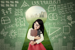Cute student with book on the keyhole Royalty Free Stock Photos