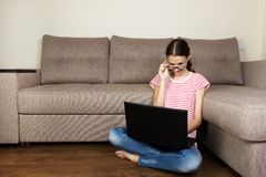 Cute student girl looking at the laptop. Young woman sitting on the floor in light appartment stock photo