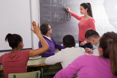 Cute student girl solves task near blackboard. In multi-ethnic classroom Royalty Free Stock Images