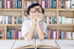 Cute student with glasses daydreaming in library Stock Images