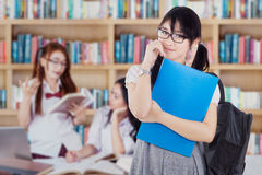Cute student with her team in the library Royalty Free Stock Image