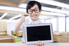 Cute student shows tablet and thumb up Stock Photo