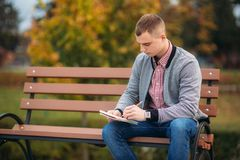 A cute student sits on the bench writes down his thoughts in his notebool using a pensil. A cute student writes down his thoughts in his notebool using a pensil Royalty Free Stock Photo