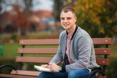 A cute student sits on the bench writes down his thoughts in his notebool using a pensil. A cute student writes down his thoughts in his notebool using a pensil Royalty Free Stock Photography