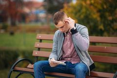 A cute student sits on the bench and writes down his thoughts in his notebool using a pensil. study outside stock image