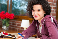 Cute student sitting at table with homework. Royalty Free Stock Photo