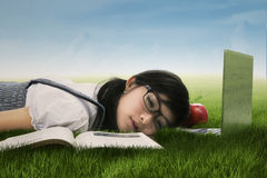 Cute student sleeping on the grass Royalty Free Stock Photography