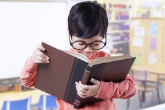 Cute student standing in class while reading book Stock Image